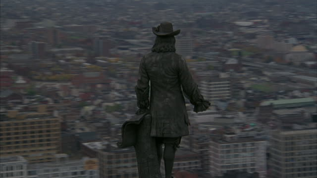 Aerial of downtown Philadelphia starting with the statue of William Penn atop city hall.