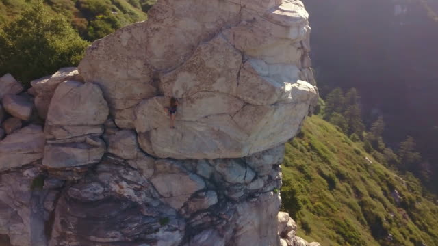 aerial of female climber on rock face - rock face stock videos & royalty-free footage