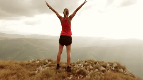 luftaufnahme von weiblichen läufer mit erhöhter hände über mountain top - herausforderung stock-videos und b-roll-filmmaterial