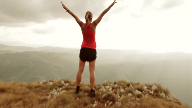 Aerial of female runner with raised hands on mountain top