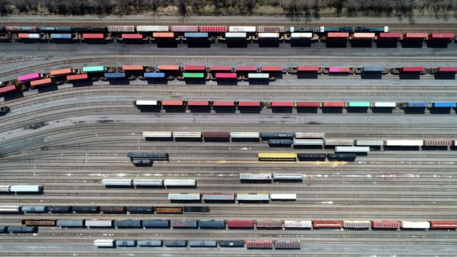 aerial of freight trains moving at depot directly above - cargo train stock videos & royalty-free footage