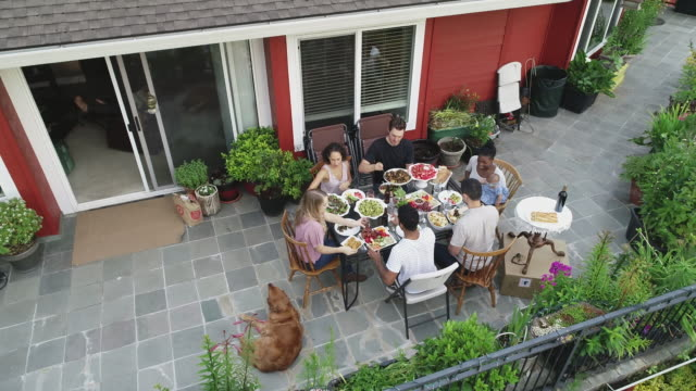Aerial of friends serving up dinner at an outdoor gathering