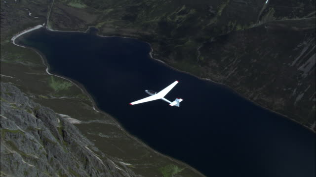 Aerial of glider over Cairngorm mountains and loch, Scotland, UK
