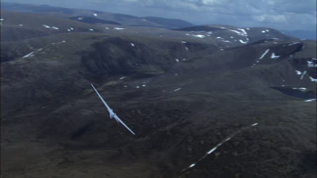 vídeos de stock, filmes e b-roll de aerial of glider over cairngorm mountains and loch, scotland, uk - planador