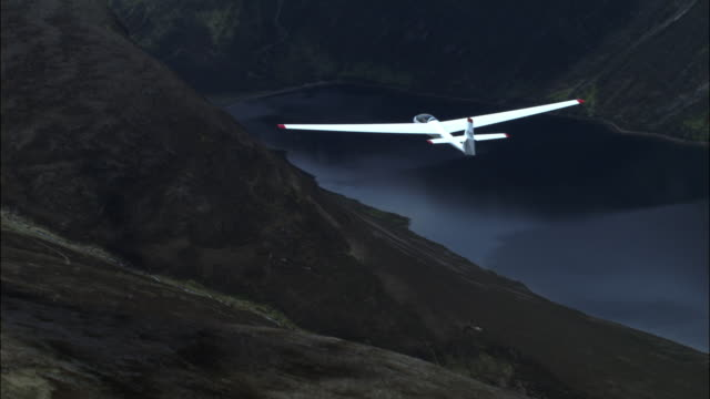 aerial of glider over cairngorm mountains and loch, scotland, uk - glider stock videos & royalty-free footage