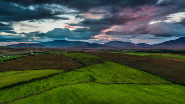 Aerial of green fields under moody sunset sky in Ireland