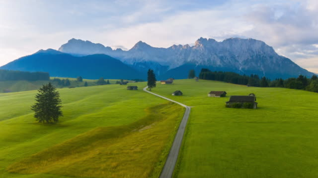 ws aerial of hay barns and karwendel mountains at sunrise - karwendel mountains stock videos and b-roll footage