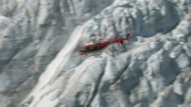 Aerial Of Helicopter Flying Over Glacier