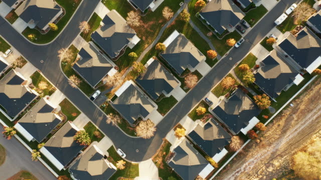 aerial of homes in autumn sunlight - drone point of view stock videos & royalty-free footage