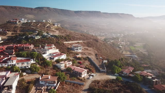 aerial of houses on the hill in baja mexico - village stock videos & royalty-free footage