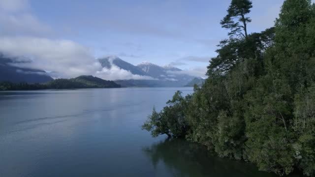 vídeos de stock, filmes e b-roll de aerial of lake and mountains with clouds - forma da água