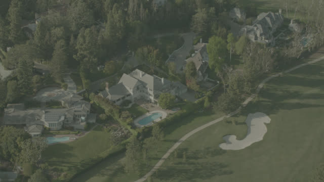 Aerial of large estate mansions with swimming pools and neighboring golf course. could be in Brentwood area of Los Angeles. trees, greens, fairways, sand traps, bunkers. upper class..