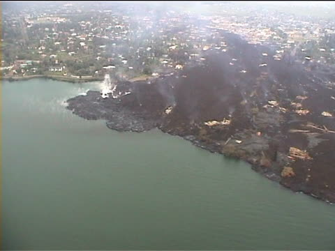 aerial of lava flow through towon and into the sea. goma 2002, drc - democratic republic of the congo stock videos & royalty-free footage