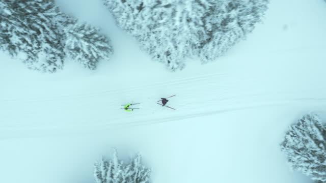 luftaufnahme von mann und frau cross country ski - draufsicht stock-videos und b-roll-filmmaterial
