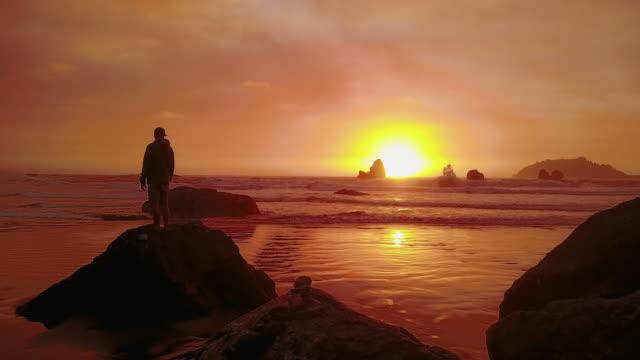 aerial of man enjoying rock at houda beach - white cap stock videos & royalty-free footage