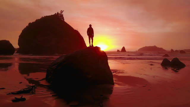 Aerial of Man Standing on a Rock at Sunset