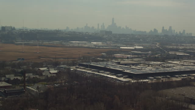 Aerial of Manhattan skyline in the distance, shot from industrial city in New Jersey