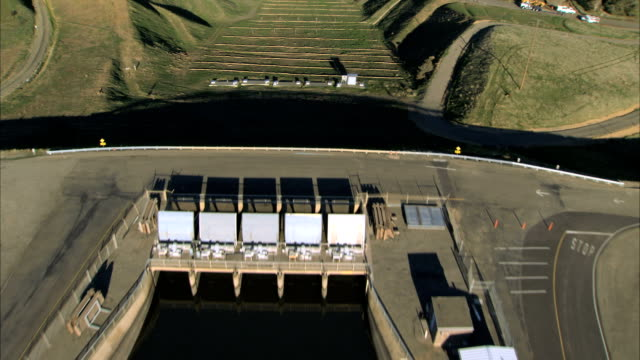 aerial of manmade irrigation chanel & hydro-electric dam - irrigation equipment stock videos and b-roll footage