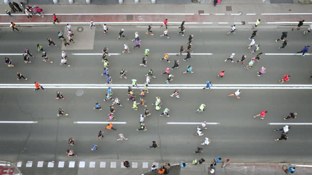 vídeos de stock e filmes b-roll de aerial of marathon participants running on main city street - imagem