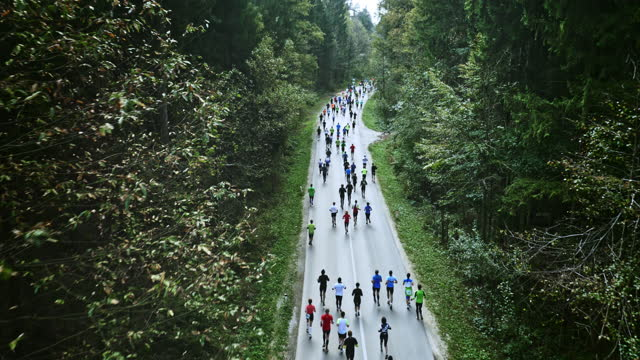 aerial of marathon participants running on road surrounded by trees - marathon stock videos and b-roll footage