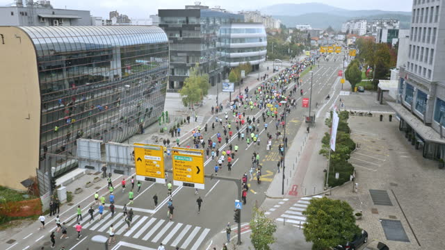 Aerial of marathon participants running through business district of city