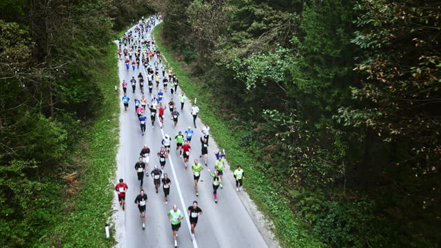 Aerial of marathon runners waving at the camera