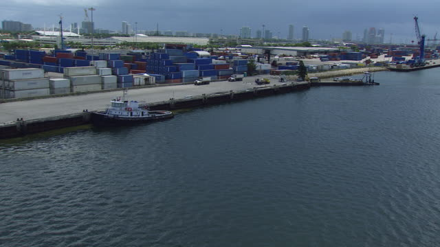 aerial of miami skyline. camera pushes in over ocean or bay to high rise hotels, condominiums, office buildings, and apartment building. speedboat visible moving towards camera leaving wake. boats moves past storage yard or shipyard with cranes and storag