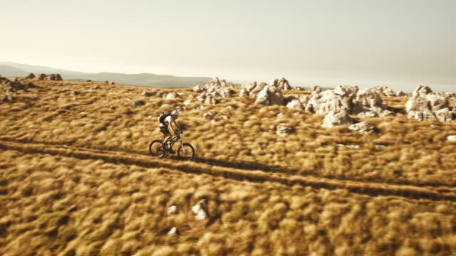 Aerial of mountain biker descending the grassy ridge
