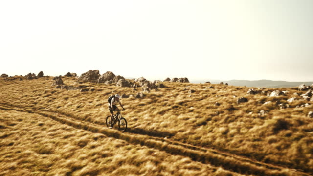 Aerial of mountain biker riding the grassy plane