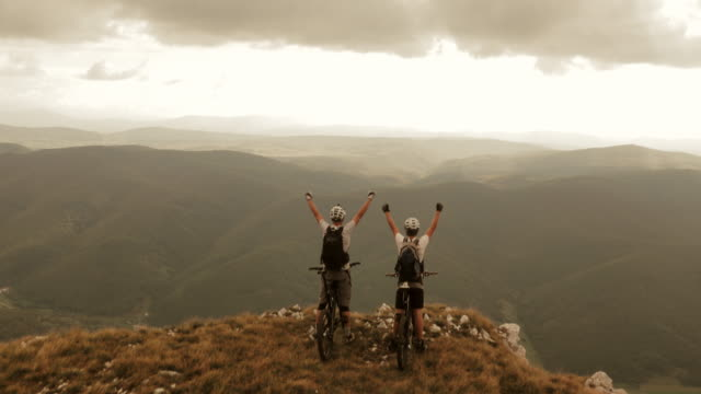 Aerial of mountain bikers on the ridge with raised hands