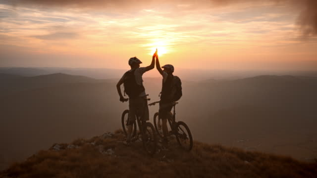 veduta aerea di ciclisti di mountain bike in cima al tramonto - avventura video stock e b–roll