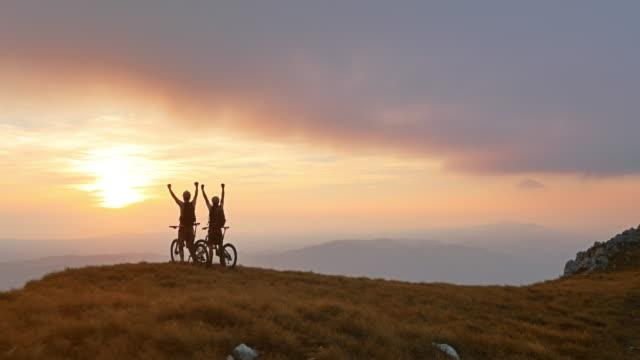 Luftaufnahme der Mountainbiker oben zu stehen und raising hands
