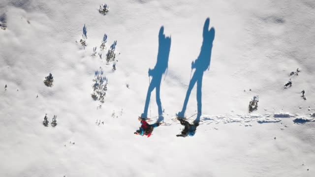 Aerial of mountaineers and their silhouettes snowshoeing on sunny day