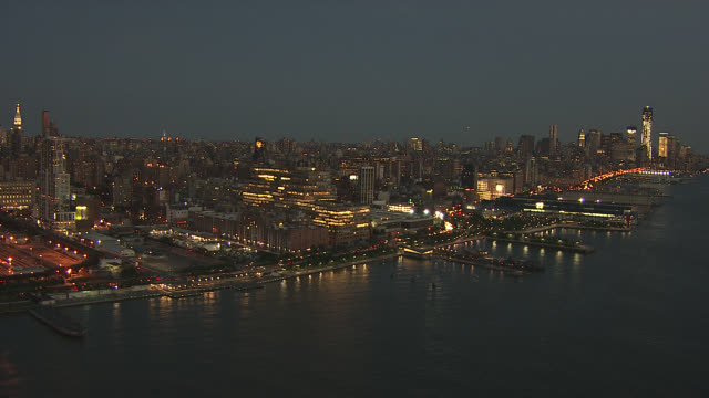 Aerial of new york city skyline, along west side, hudson river. midtown manhattan. empire state building lit up with green lights visible. skyscrapers and high rise office or apartment buildings. landmarks. new yorker hotel visible in bg. cars and traffic.