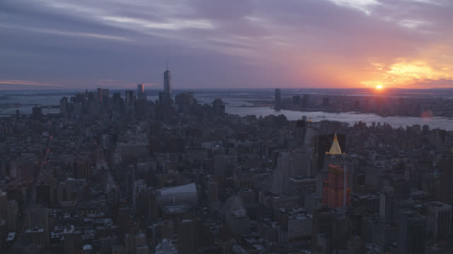 aerial of new york city skyline at sunset. rivers visible. freedom tower, empire state building, and chrysler building visible.