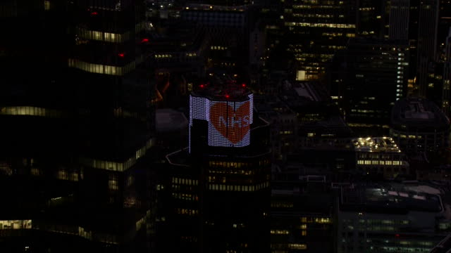 aerial of nhs sign lit up on london skyscraper as people thank the nhs during clap for carers event during coronavirus crisis - luminosity stock videos & royalty-free footage