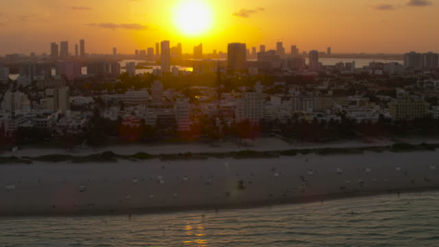 Aerial of ocean, beach, buildings and hotels South Beach sunset Miami, FL