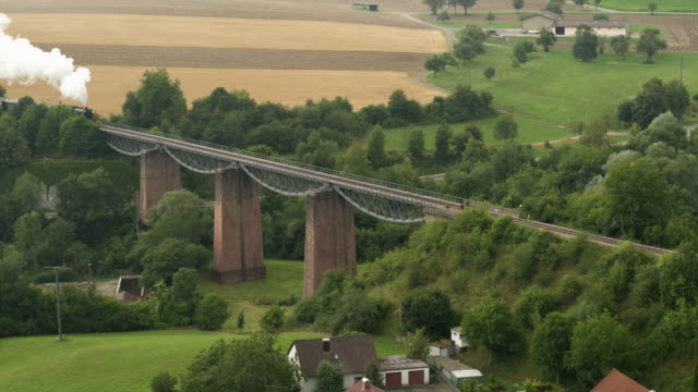 aerial of old steam train on a bridge - locomotive stock videos & royalty-free footage