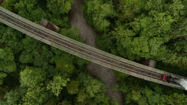 aerial of old steam train on a trestle from above looking down - railway bridge stock videos & royalty-free footage