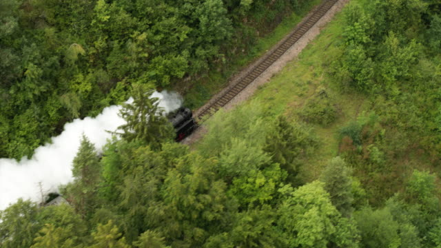 aerial of old steam train with billowing smoke stack from behind - steam train stock videos & royalty-free footage