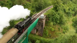 Aerial of old steam train with billowing smoke stack from behind