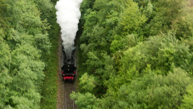 aerial of old steam train with billowing smoke stack from the front - locomotive stock videos & royalty-free footage