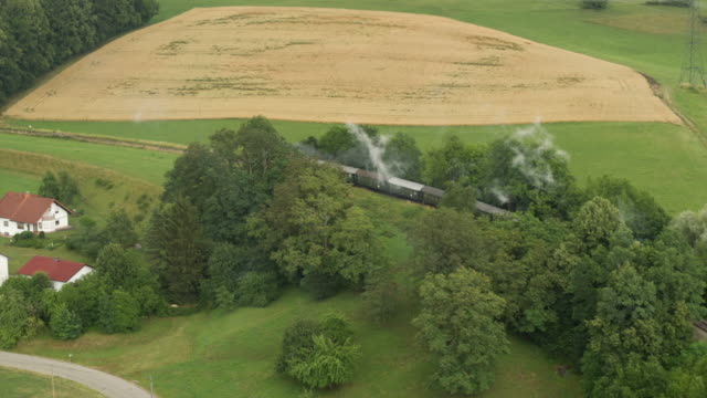 aerial of old steam train with billowing smoke stack in the countryside - steam train stock videos & royalty-free footage