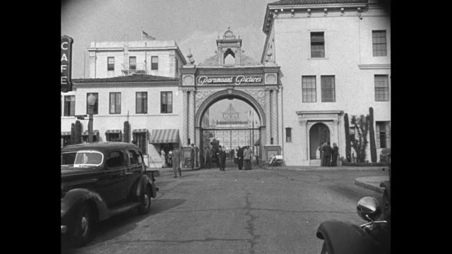 aerial of paramount studios in hollywood / iconic paramount pictures gate / diminutive zukor talks with paramount workers / zukor on a movie set with... - hollywood stock videos & royalty-free footage
