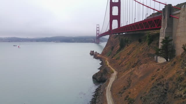aerial of path beside golden gate bridge - baia di san francisco video stock e b–roll