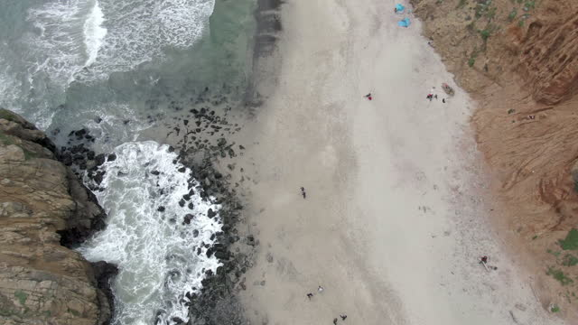aerial of people by famous keyhole arch at pfeiffer beach, drone descending over natural landmark splashing waves - big sur, california - natural landmark stock videos & royalty-free footage
