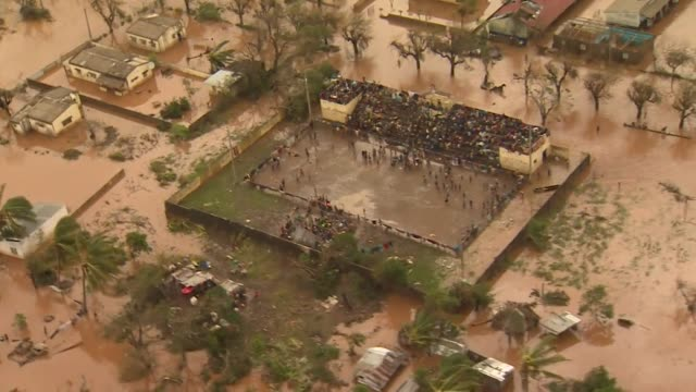Aerial of people sheltering in stands of stadium surrounded by flood water after Cyclone Idai in Buzi Mozambique