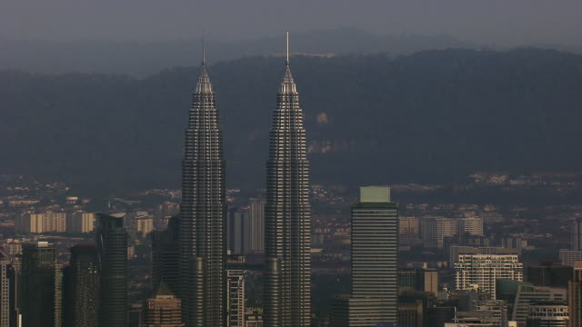 aerial of petronas towers in kuala lumpur - petronas twin towers stock-videos und b-roll-filmmaterial