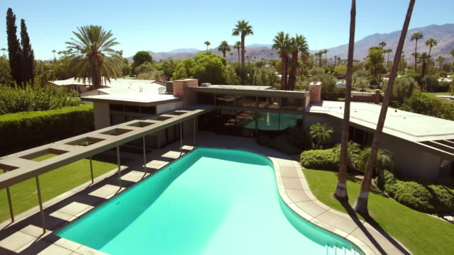 ws aerial of piano shaped swimming pool at the 1947 sinatra home - palm springs california stock videos & royalty-free footage