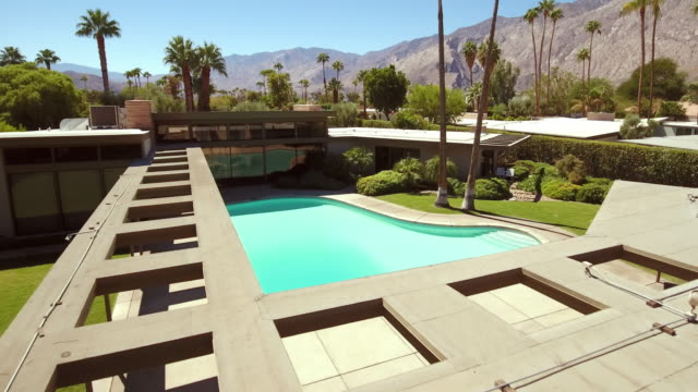 ws aerial of piano-shaped swimming pool and canopy skylight entryway at sinatra home from 1947 - palm springs california stock videos & royalty-free footage